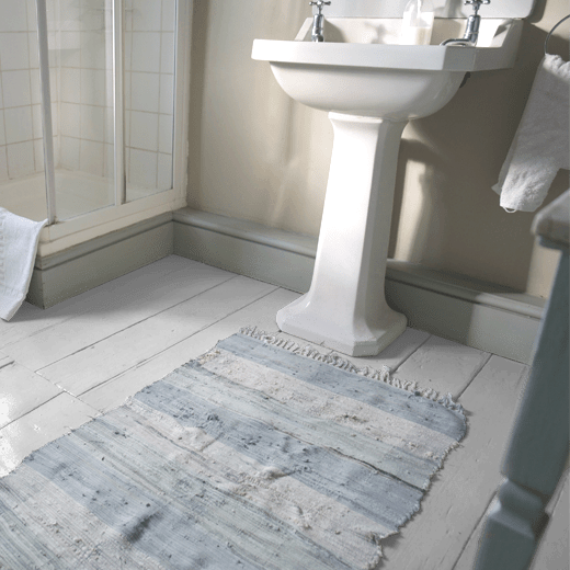 Mauve Roses by Designers Guild on bathroom floorboards
