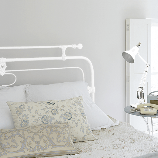 Stone-Pale-Cool by Little Greene on a metal bedstead and lamp